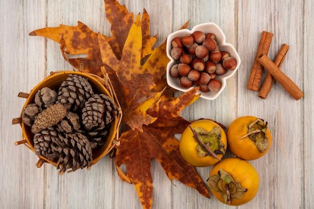 灰色の木製のテーブルにシナモンスティックとボウルにヘーゼルナッツの葉とバケツの松ぼっくりの上面図