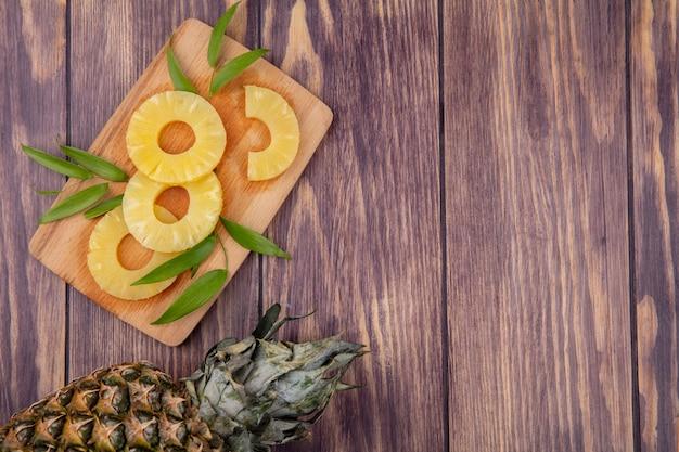 커팅 보드와 나무 표면에 잎 파인애플과 조각의 상위 뷰