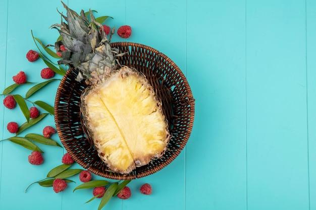 Вид сверху на половину ананаса в корзине с узором из малины и листьев на синей поверхности