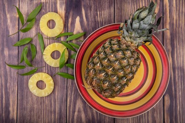 パイナップルスライスと木の表面に葉をボウルにパイナップルのトップビュー