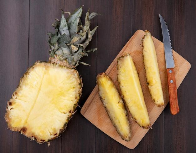 パイナップルのスライスと木製の表面に半分パイナップルとまな板の上のナイフのトップビュー