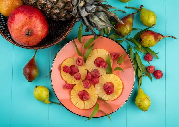 パイナップルスライスとザクロのパイナップルのバスケットとプレートのラズベリーと青の表面に周りの葉と桃のトップビュー