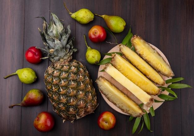나무 표면에 전체 하나와 복숭아 사과와 함께 접시에 파인애플 슬라이스의 상위 뷰