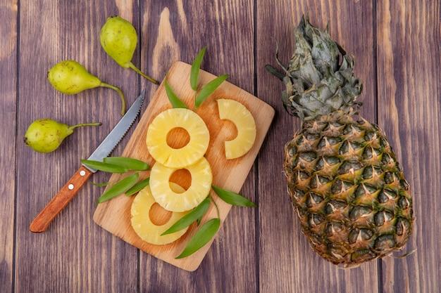 Вид сверху на ломтики ананаса с листьями на разделочной доске и ананас-персик с ножом на деревянной поверхности