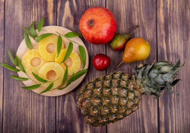 Вид сверху ломтиков ананаса с листьями на разделочной доске и ананасом, гранатом, персиком, сливой на деревянной поверхности
