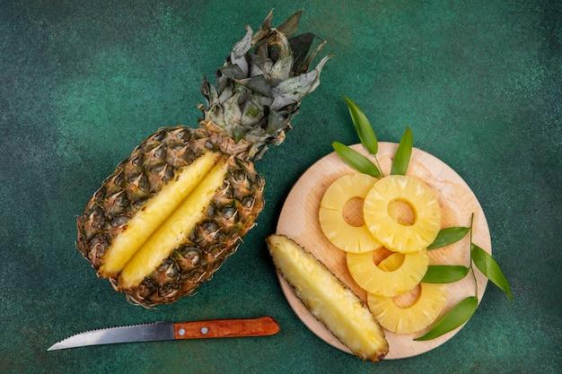 Вид сверху ананаса с одним кусочком, вырезанным из целых фруктов и ломтиков ананаса на разделочной доске с ножом на зеленой поверхности