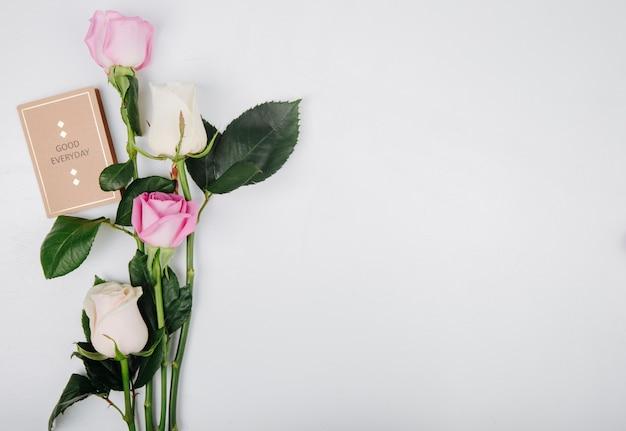 Вид сверху розовых и белых цветных роз с небольшой открыткой на белом фоне с копией пространства