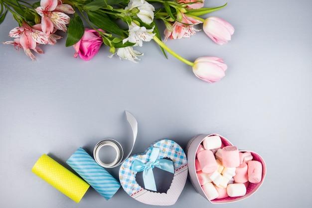 ピンクと白の色のチューリップとアルストロメリアとハート型のプレゼントボックスとバラの花の上面図は、白いテーブルにマシュマロでいっぱい