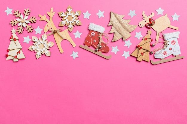 お祝いおもちゃとクリスマスシンボルトナカイと新年の木で飾られたピンクの背景の平面図です。コピースペースと休日の概念