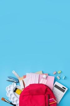 파란색 테이블 배경 위에 학교 문구류가 있는 분홍색 배낭의 맨 위 보기, 다시 학교 디자인 개념으로 돌아갑니다.