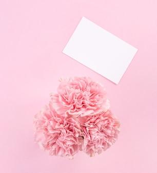 ピンクのテーブルの背景にピンクのカーネーションの上面図