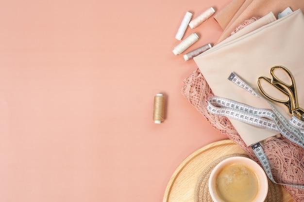 ピンクの珊瑚色のレースと糸のスプール、メモ帳の計算機、巻尺、ピンクの背景のコーヒーの近くのはさみの仕立てのシルク生地の上面図。イブニングドレスの縫製コンセプト。
