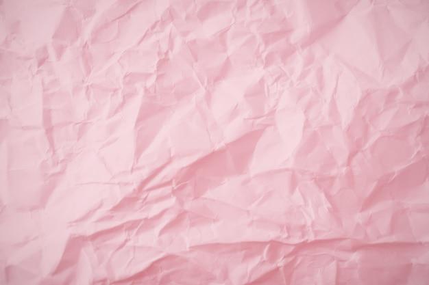 ピンクのしわくちゃの紙の背景の平面図です。