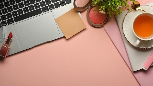 ノートパソコン、化粧品、ティーカップ、文房具、コピースペースを備えたピンクのフェミニンなクリエイティブワークスペースの上面図