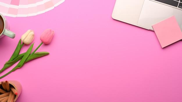 ラップトップ、メモ帳、ペイントツール、チューリップの花、コピースペースを備えたピンクのフェミニンなフラットレイワークスペースの上面図