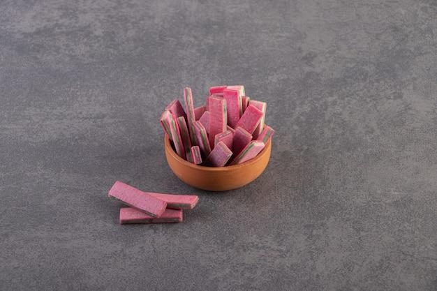 灰色の表面上のボウルのピンクのガムの上面図