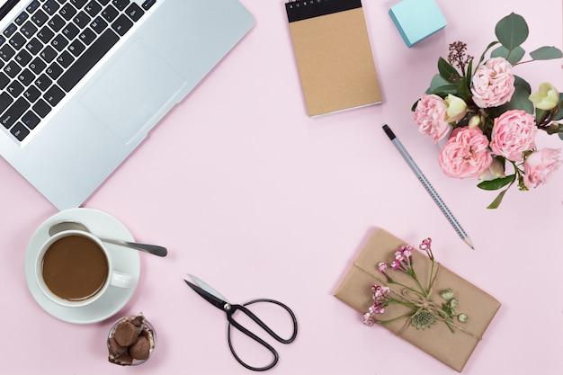 노트북, 스마트 폰, 커피와 꽃의 컵 핑크 사무실 책상 테이블의 상위 뷰. 공간을 복사하고 평평하게 놓습니다.