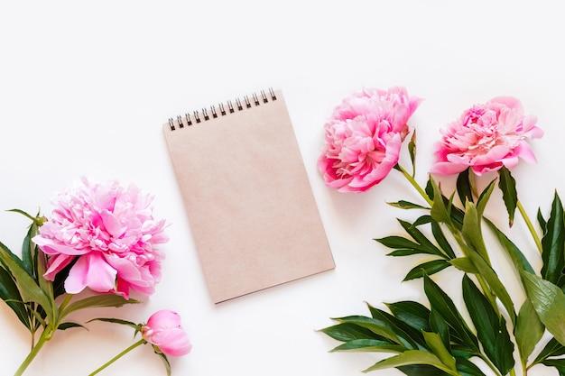 コピースペース付きのノートブックとピンクの牡丹の花の平面図です。