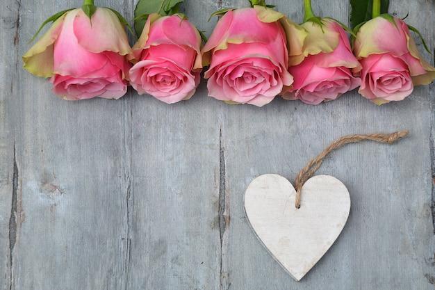 木製の表面にテキスト用のスペースとハートの木製タグとピンクのバラの花の上面図
