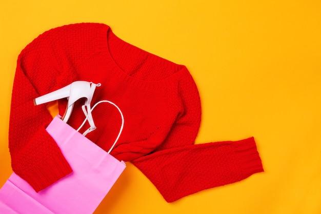 Вид сверху розовой хозяйственной сумки с красным swether и стильной обувью. понятие моды и дизайна, шоппинг