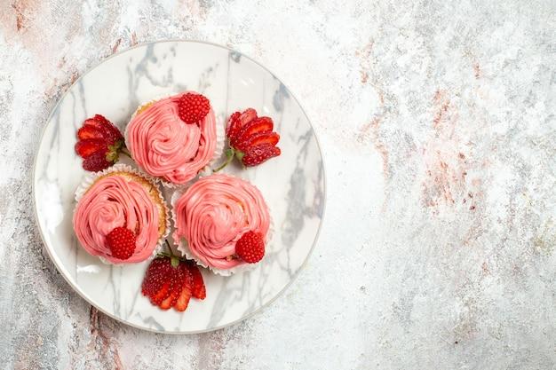 白い表面に新鮮な赤いイチゴとピンクのストロベリーケーキの上面図
