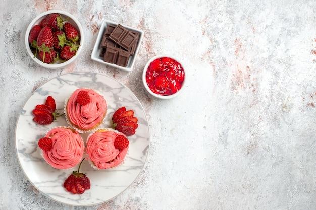 白い表面にジャムとチョコレートバーとピンクのストロベリーケーキの上面図