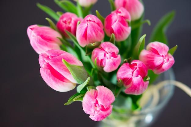 花瓶に緑の葉を持つピンクのチューリップの上面図