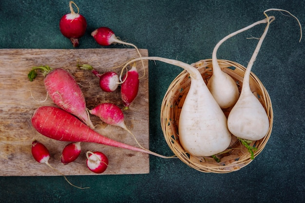 緑の背景の上のバケツに白いビートルートと大根と木製のキッチンボード上のピンクがかった赤い根菜ビートルートの上面図