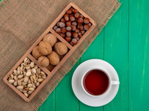 Вид сверху фисташек с фундуком и грецкими орехами на бежевой салфетке с чашкой чая на зеленой поверхности