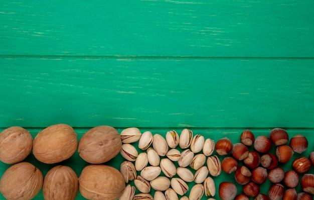 Вид сверху фисташек с фундуком и грецкими орехами на зеленой поверхности
