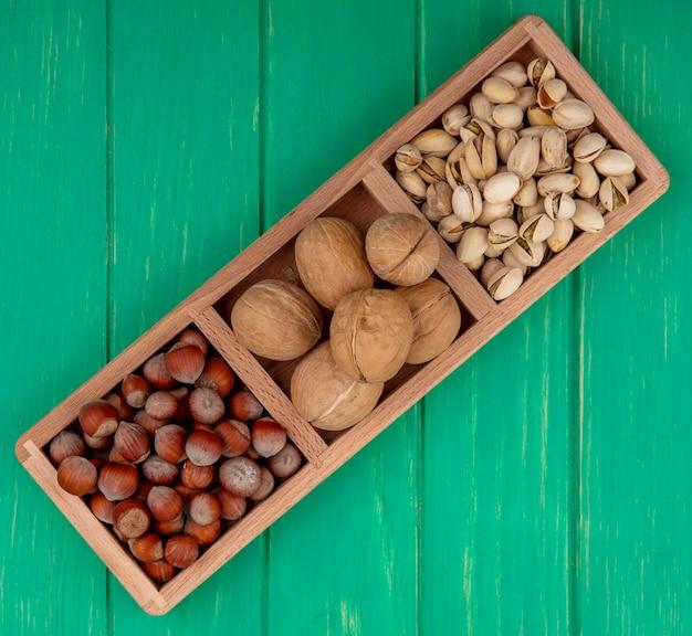 Вид сверху фисташек с фундуком и грецкими орехами на деревянной подставке на зеленой поверхности