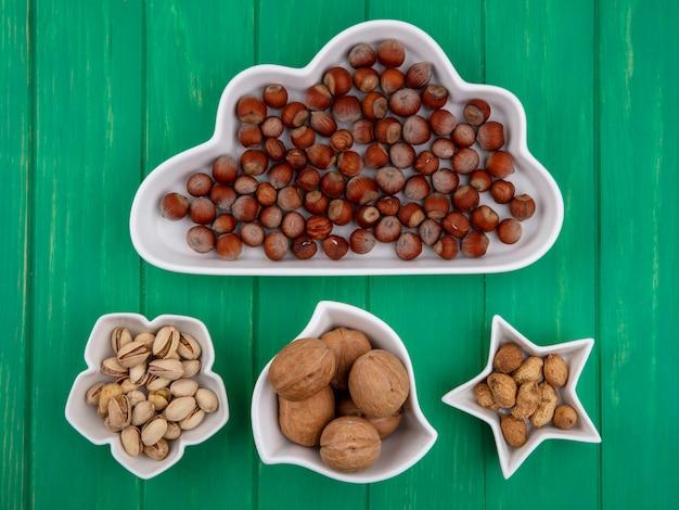 Вид сверху фисташек с фундуком, грецкими орехами и арахисом в мисках разной формы на зеленой поверхности