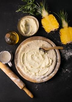 Вид сверху на тесто для пиццы в миске с ананасом