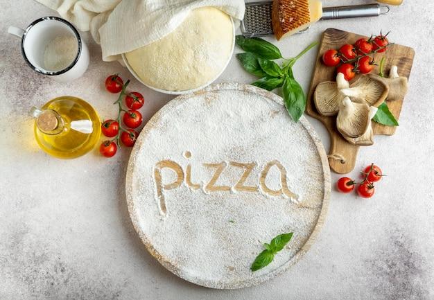Вид сверху на тесто для пиццы с грибами и помидорами и слово, написанное в муке