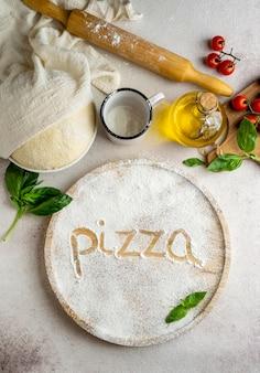 Вид сверху на тесто для пиццы с помидорами и словом, написанным в муке
