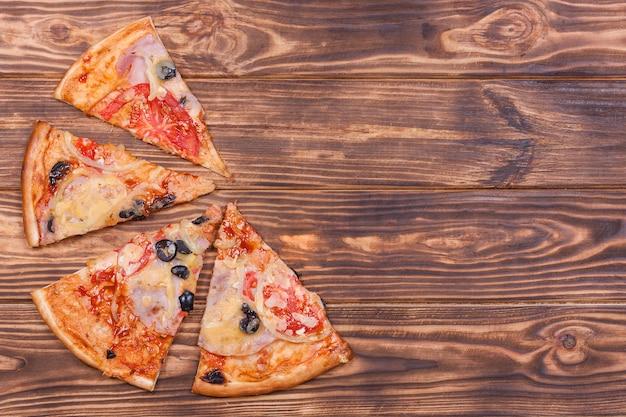 木製のテーブルの背景にトマト、ブラックオリーブ、ハム、タマネギとピザスライスの上面図