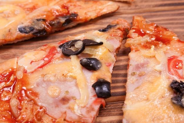 木製のテーブルの極端なクローズアップにトマト、ブラックオリーブ、ハム、タマネギとピザのスライスの上面図