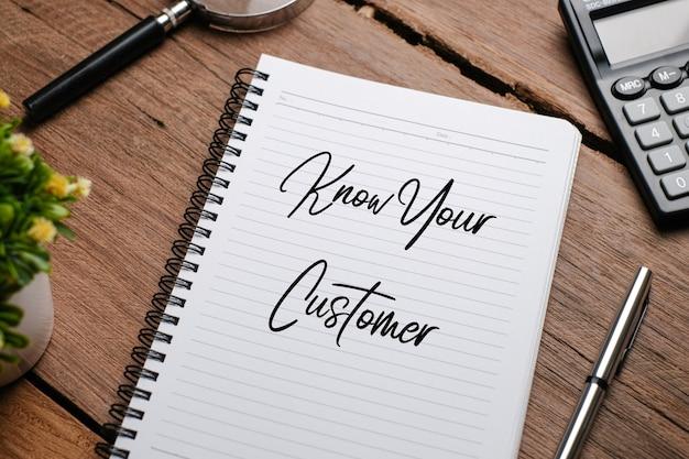 식물, 안경, 시계, 손을 잡고 펜을 들고 나무 배경 위에 '우리 고객이 말하는 것'을 칠판에 쓴 최고의 전망.