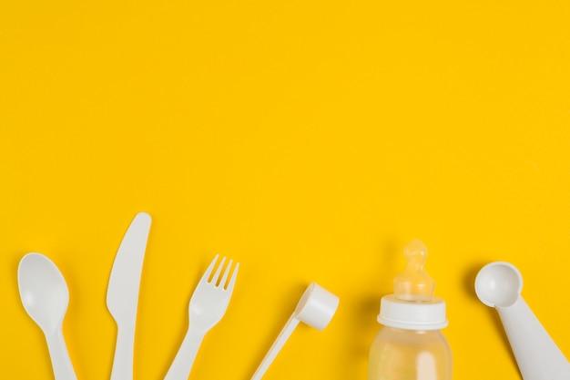 Вид сверху пластиковых столовых приборов и детской бутылочки для детского душа