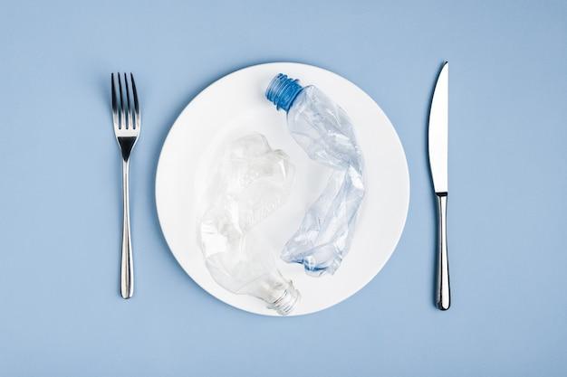 白いプレート、ナイフ、フォークのプラスチック廃棄物ゴミの上面図、問題から環境を保護します
