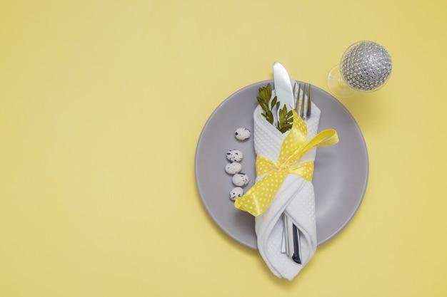 Вид сверху на тарелку, столовые приборы и стакан с пасхальным яйцом на желтом столе с копией пространства