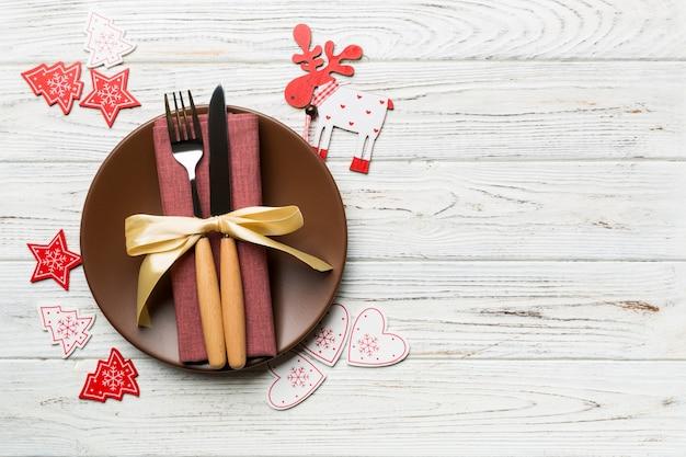 접시, 포크, 나이프의 상단 전망은 크리스마스 장식된 나무 배경에서 제공됩니다. 복사 공간 새 해 이브 개념입니다.