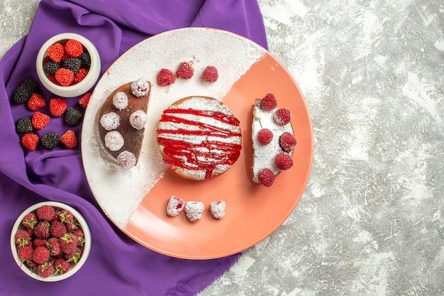 Вид сверху тарелки десерта на фиолетовой салфетке с ягодами сбоку на мраморном фоне