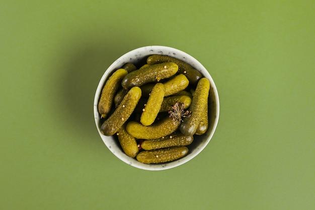 緑の表面にガーキン、きゅうりのピクルスのプレートの上面図。きれいな食事、ベジタリアン料理のコンセプト