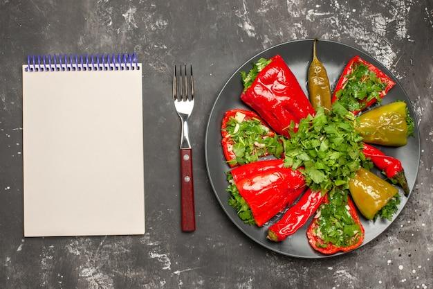 Вид сверху на тарелку перца перца с зеленью на тарелке белой вилки для ноутбука