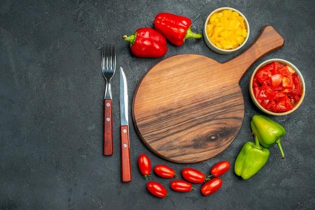 濃い灰色の背景にカトラリーと野菜のプレートスタンドの上面図
