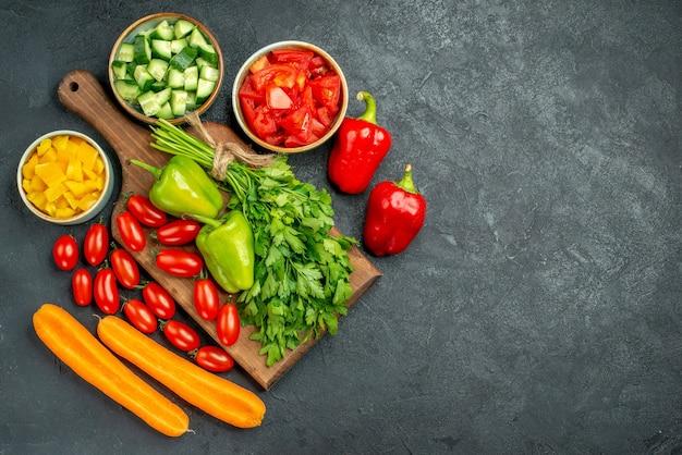 Вид сверху на подставку для тарелок с овощами над ней и рядом с ней и свободное место для текста на темно-сером фоне
