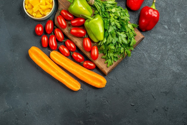 濃い灰色の背景にあなたのテキストのための自由な場所でその上と近くに野菜とプレートスタンドの上面図
