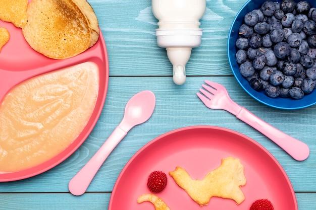 Вид сверху тарелки с детским питанием и черникой