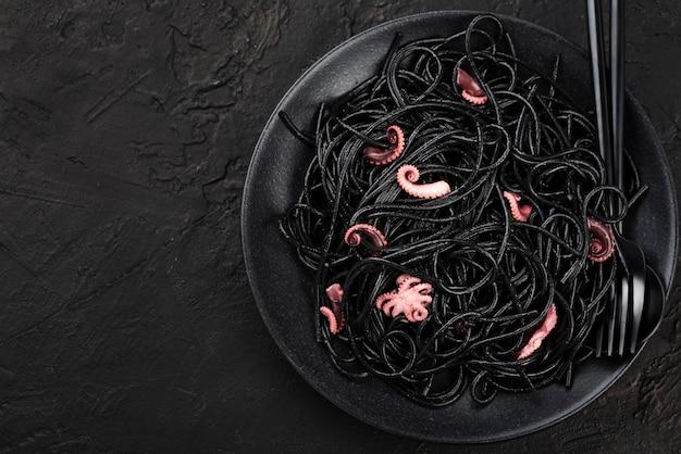 Вид сверху тарелка с черными спагетти и кальмарами